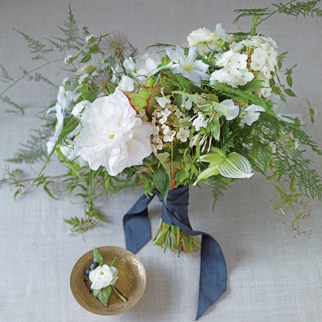 A feminine bridal bouquet looks effortless when the aesthetic isn't overly designed. A loose, picked-from-the-field bouquet of white flowers mixed with ferns and vines is undone but elegant.