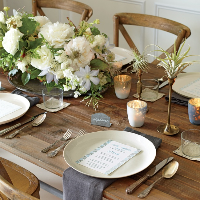 Layering raw materials like wood, metal and linen napkins adds texture to a neutral, natural color palette. Big blooms in ivory and white displayed on vintage metallic platters dress up the country vibe without being too fancy.
