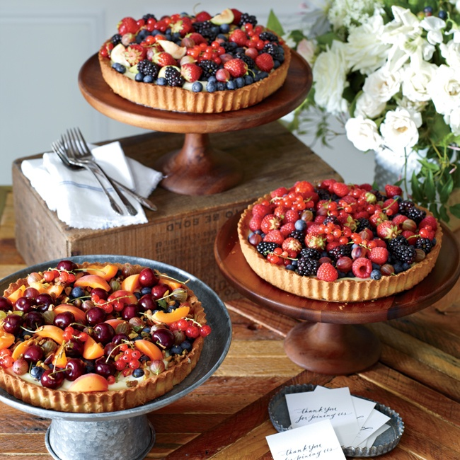 Even dessert tables can take inspiration from nature. Set atop wood and antique metal stands, custard pies topped with fresh berries and fruit further the fresh, down-home feel.