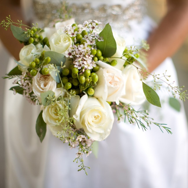 The bride had no particular bouquet in mind, so her florist created a loose, romantic bouquet with white roses and green leaves and berries.