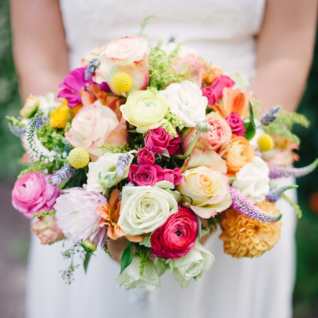 The bride's bright bouquet consisted of spray and garden roses, ranunculuses, dahlias, lavender and billy balls in pinks, oranges and white.