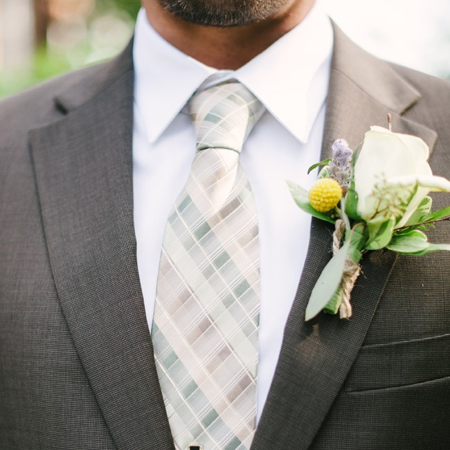 The groom wore a gray suit and neutral colored plaid tie from Men's Wearhouse. His boutonniere included a white rose, billy ball and sprig of lavender.