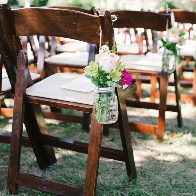 Decor at the ceremony was kept simple: Mason jars filled fresh pink and green flowers hung on the end of each row of chairs.