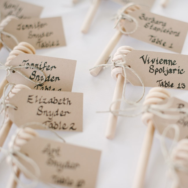 Escort cards—which the bride's aunt wrote in calligraphy—were tied to honey dippers as a complement to the honey jar favors.