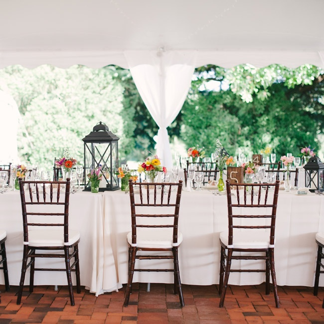 The reception was held under a large tent on the brick patio. Eclectic decorations and ivory tablecloths gave the space a relaxed but energetic feel.