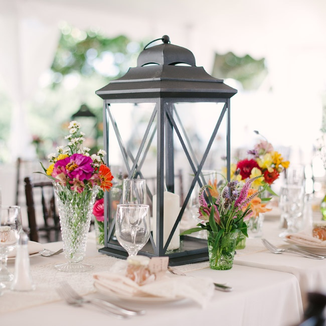Lanterns filled with white candles were surrounded by a mix of vases filled with colorful flowers that matched those in the bride's bouquet.