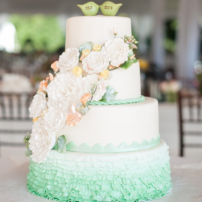 Inspired by cakes she saw on Pinterest, Erin chose and green and white cake with ombre ruffles, sugar flowers cascading down the side and bird toppers.