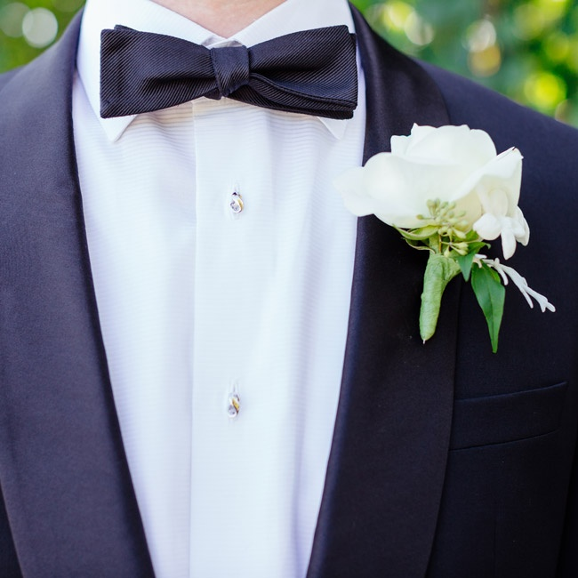 "Luke stuck with a classic look: He wore a slim-fit black tuxedo with a white shirt and black bow tie. (""Very slick,"" his now-wife says.) A white rose boutonniere decorated his lapel."