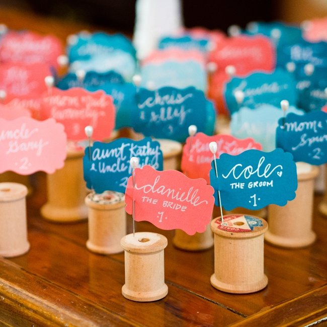 Pearl topped pins held the escort cards and were stuck into vintage spools for a subtle nod to the bride's love of embroidery.