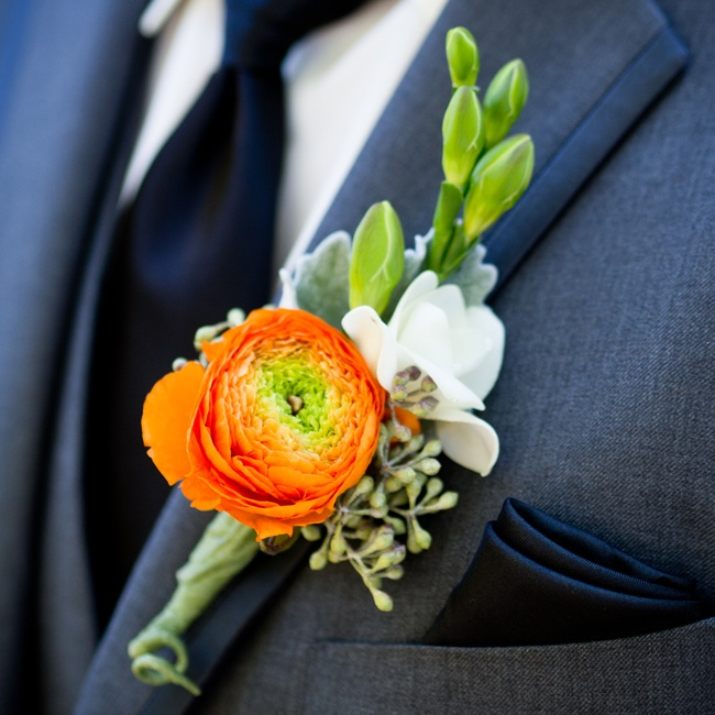 A bright orange ranunculus, paired with a crisp white freesia, added a burst of color to the groom's lapel.