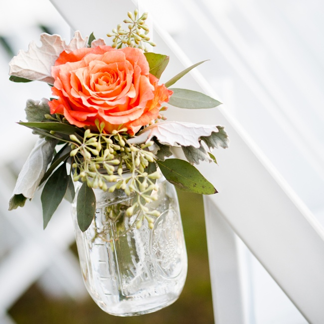 Mason jars filled with coral roses, seeded eucalyptus and dusty miller, decorated the ceremony aisle.