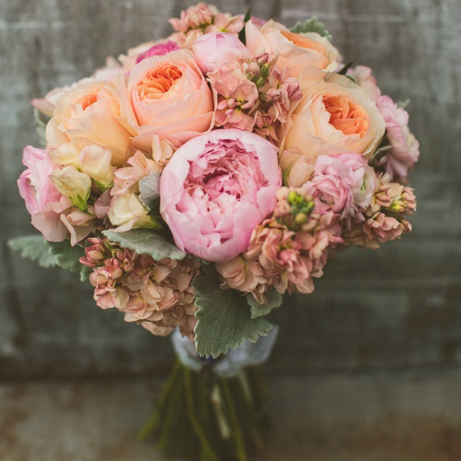 The bride's favorite color, pink, was incorporated into the florals, with light pink peonies, peach garden roses and ivory-pink stock flowers in her bouquet.