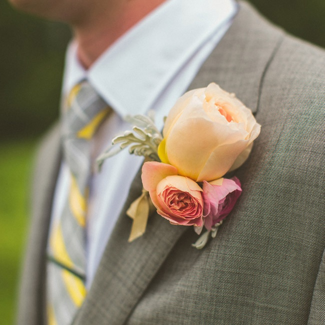 The groom wore a boutonniere with three pink and peach garden roses with dusty miller.