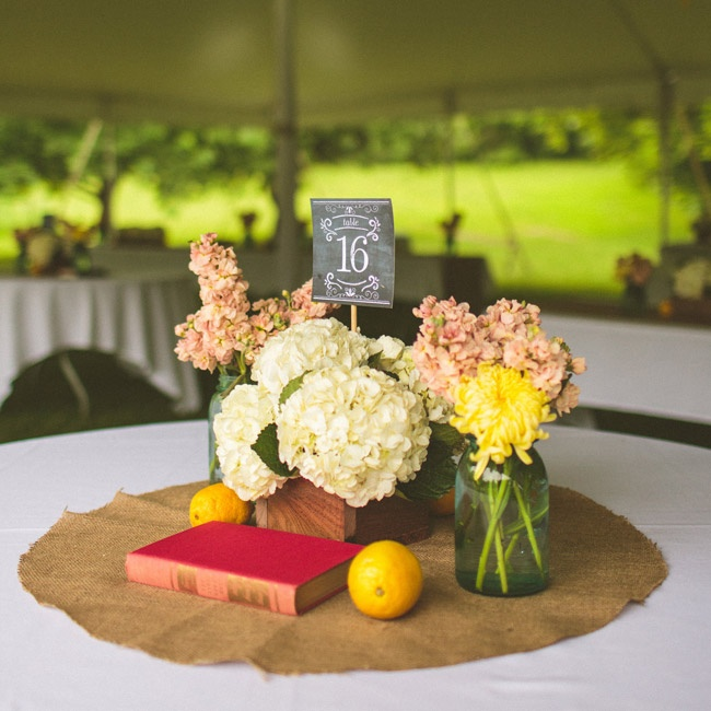 Boxes filled with white hydrangeas were moved from the ceremony aisle to the dinner tables for the reception. The arrangements were surrounded by vintage books, fruit and mason jars filled with a few flowers.