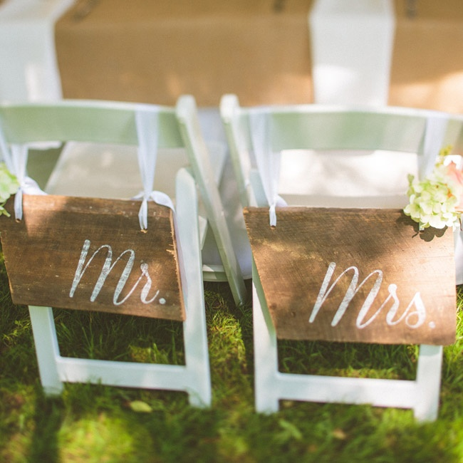 "Slabs of wood labeled ""Mr."" and ""Mrs."" hung on the backs of the bride and groom's chairs."