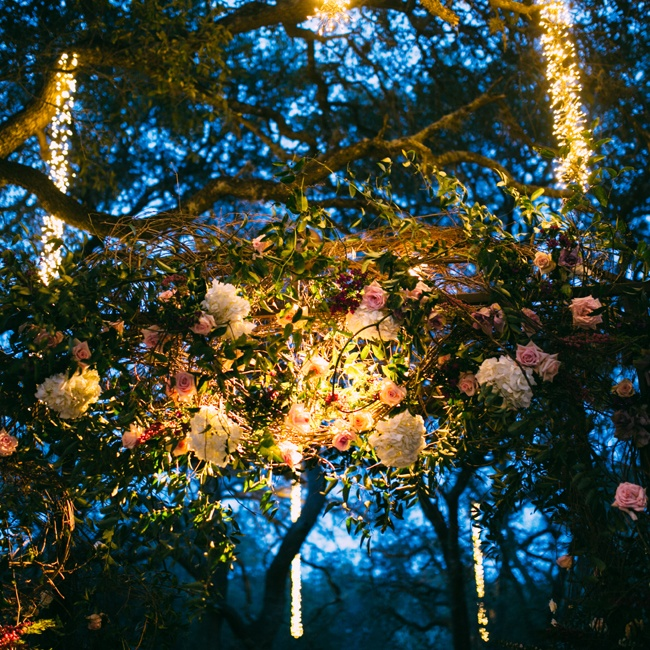 A lush arch of white and pink peonies and roses surrounded by hanging lights made the ceremony space look like a dreamy garden.