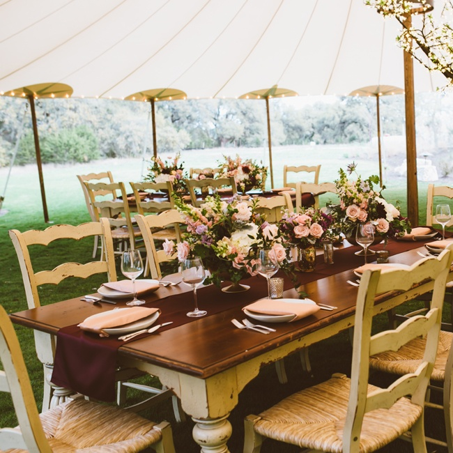 Tables with an antique look and burgundy table runners gave the reception tables a polished-rustic feel.