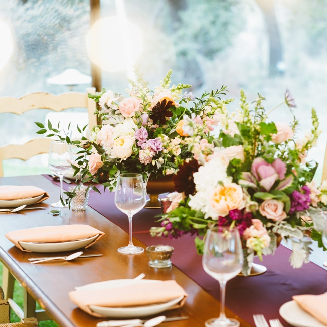 Gold vases overflowing with muted pink flowers and greenery carried the vintage garden look onto the tables.