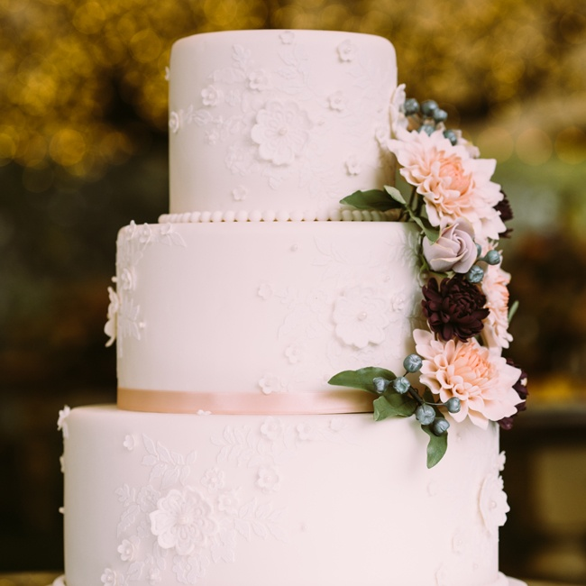 The simple white cake got a vintage makeover with lace–inspired sugar flowers and muted pink flowers cascading down the side.