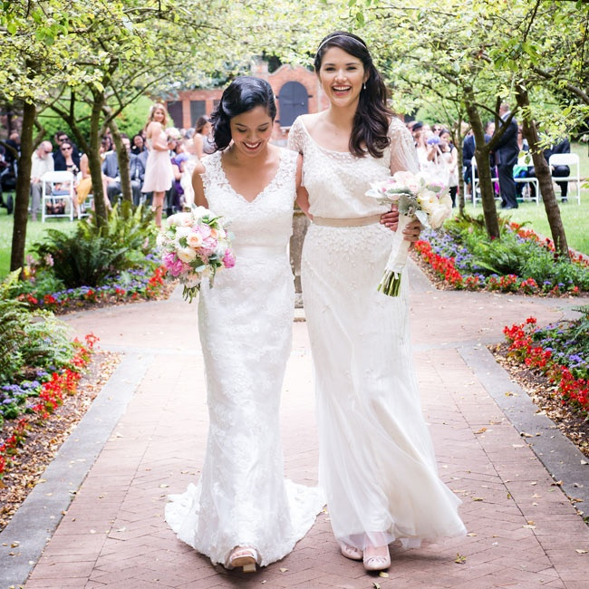 Both brides wore long, white dresses—one with romantic lace, the other with beaded details. Similar silhouettes made sure one bride's gown didn't outshine the other's.