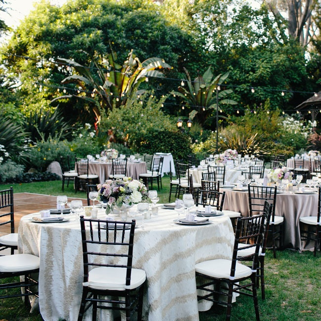 Neutral tablecloths and brown Chiavari chairs blended in with the lush garden scenery during the reception.