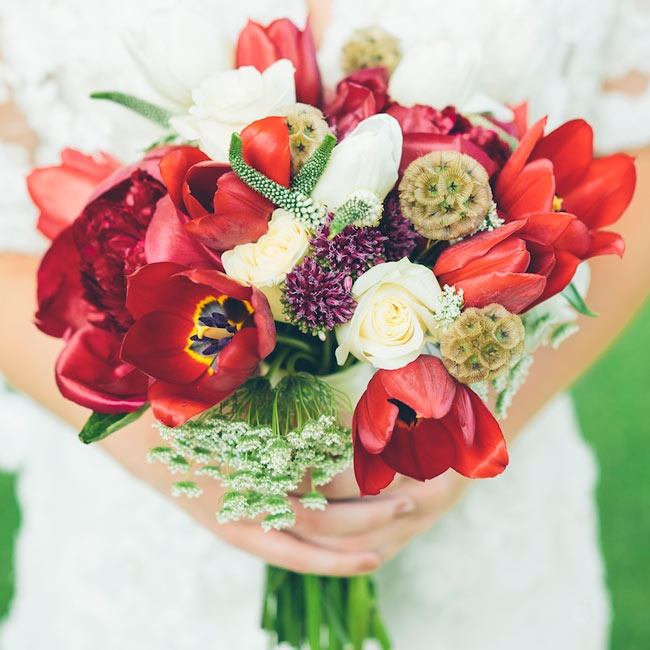 Vibrant red tulips mingled with scabiosa pods and white roses in the bride's bouquet.