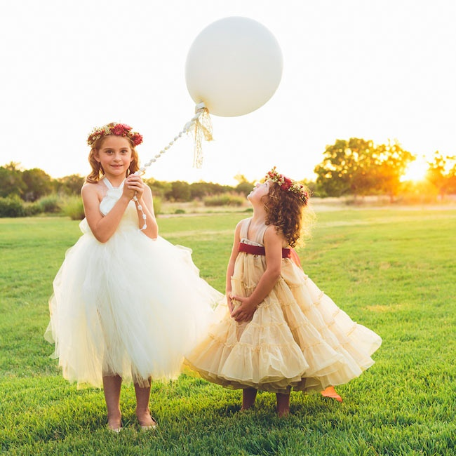In lieu of a flower basket, the flower girls held weather balloons and accessorized with floral crowns.