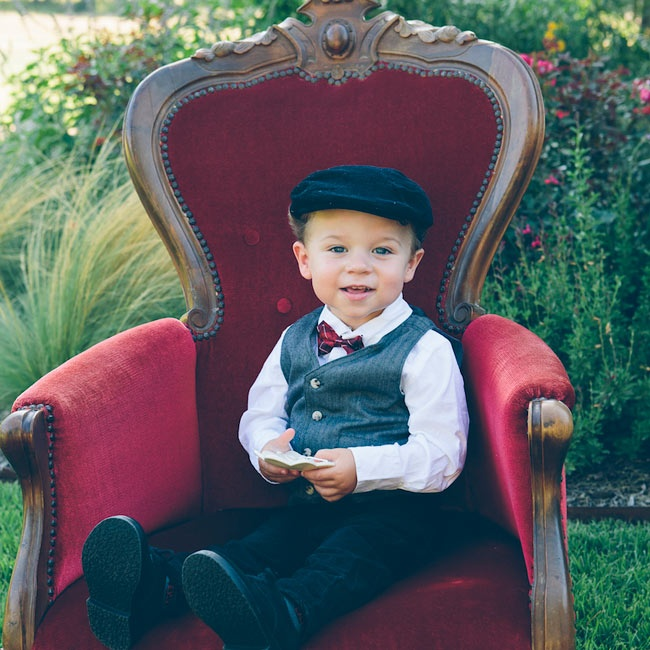 The ring bearer wore an old-fashioned look with a vest, a deep red bow tie and a newsboy cap.