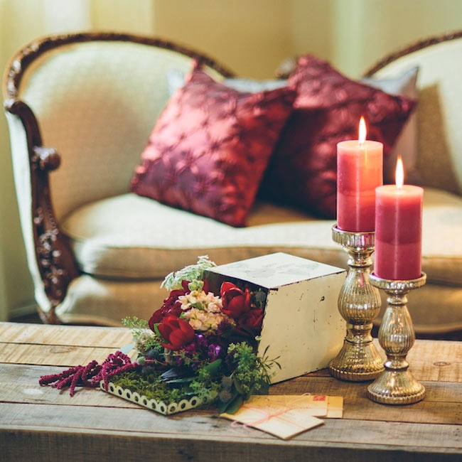 Deep red floral arrangements spilled out of an antique letter box in a French-inspired lounge area.