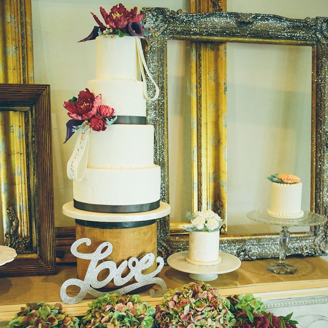 A tall, tiered cake was topped with burgundy flowers and slate ribbons.