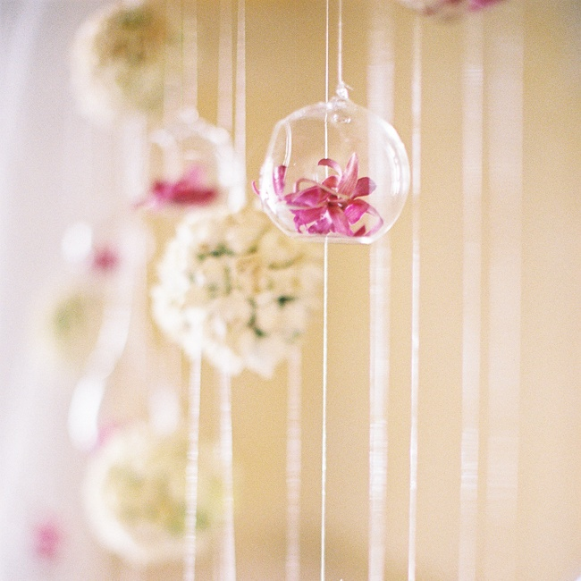 The ceremony backdrop was comprised of bright purple orchids in glass orbs and white rose pomanders.