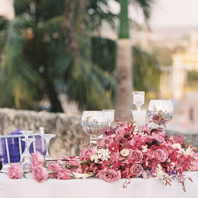 Purple orchid rose and orchid centerpieces complemented the colors of the setting Colombian sunset.