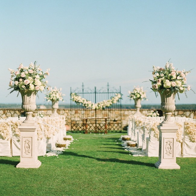 Ornate stone pillars stood at the entrance to the ceremony. The urns were filled with ivory and blush hydrangeas and roses for a traditional, romantic look.