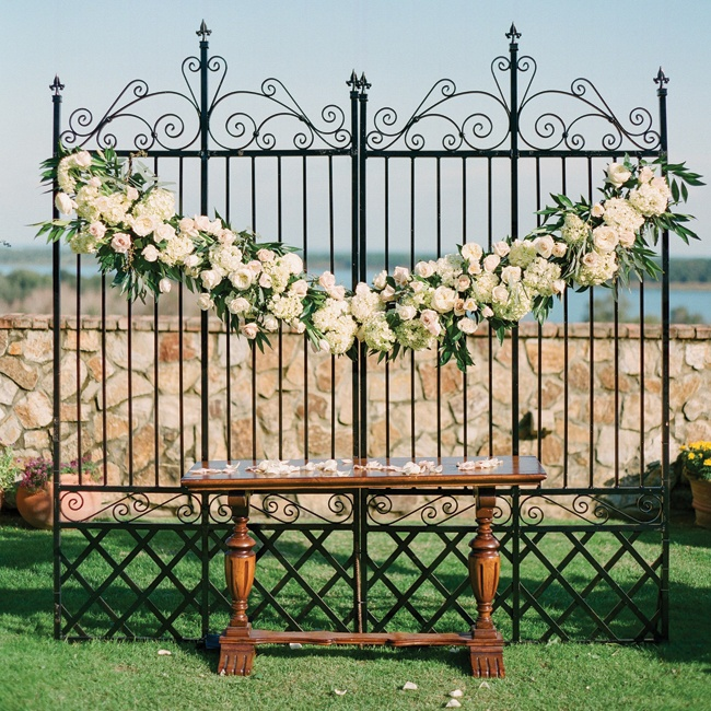 A floral garland draped over a wrought iron backdrop added a romantic, vintage aesthetic to the ceremony.