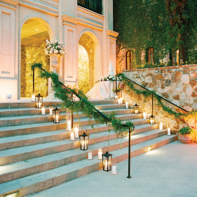 Lanterns and white pillar candles cast a warm, romantic glow over the stone steps.