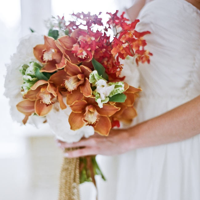 In her bridal bouquet, Tess mixed red and orange orchids for a textured feel against simple white peonies.