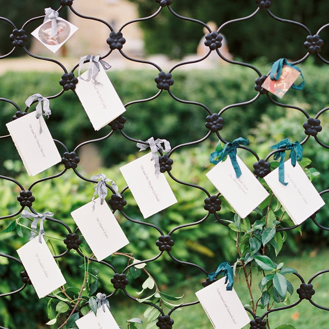 Escort cards were tied in varied ribbon colors to an ornate fence near the castle.
