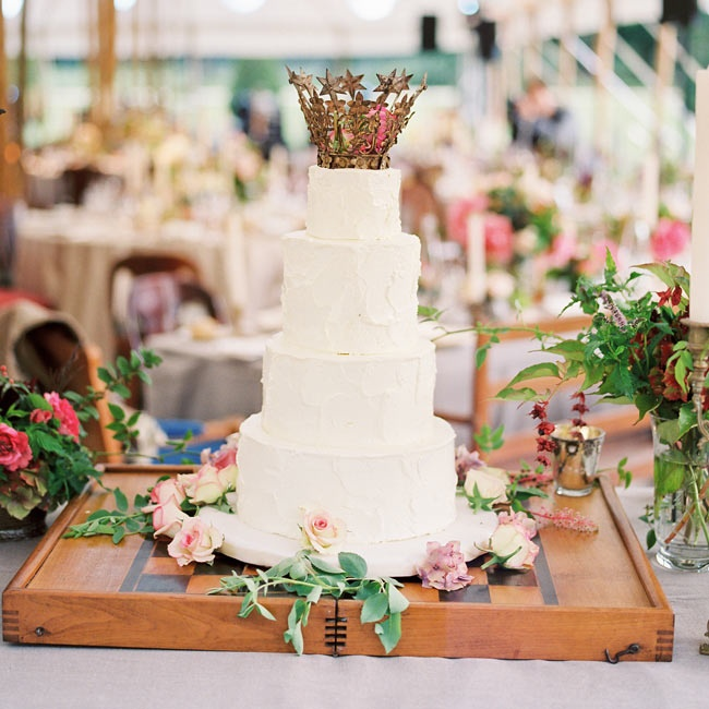 The tiered white wedding cake was traditional in style and color, but was also topped with a sparkling gold crown.