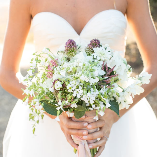 The bride carried a textured bouquet of white flowers mixed with thistles.