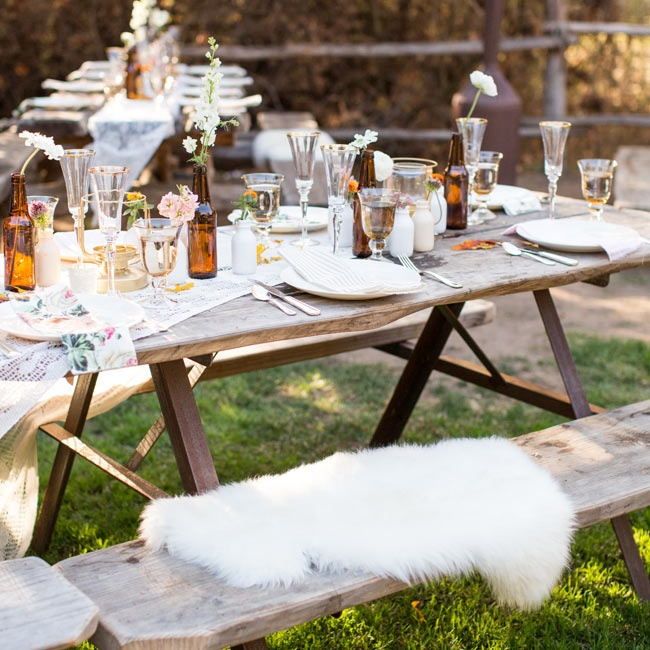 Each rustic wooden picnic tables had white fur lining each seat.