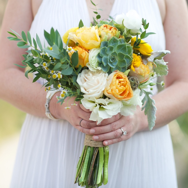 Pops of yellow roses mixed with dusty miller and vibrant green succulents in the bridal bouquet.