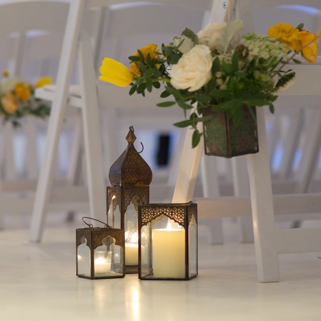 Vintage-inspired lanterns in groups of three lined the ceremony aisle along with potted bouquets of yellow, white and green floral arrangements.