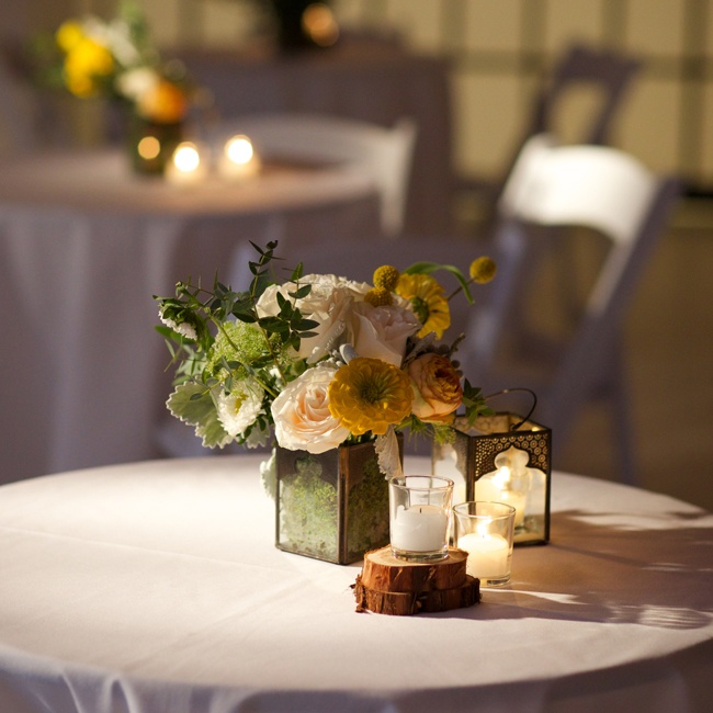 Yellow ranunculuses, billy balls and white roses blended together at each table and were surrounded by tea lights.