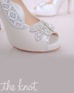 White silk satin peep-toe platform pump features rhinestone jewel and full Poron® padded insole with built-in arch support. Sizes 5-10