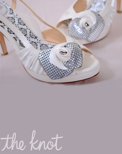 "White and silver silk satin peep-toe platform slingback features 3 or 4"" heel, pearlescent ivory patent leather straps, chain mesh rosette, and full Poron® padded insole with built-in arch support. Sizes 5-10"