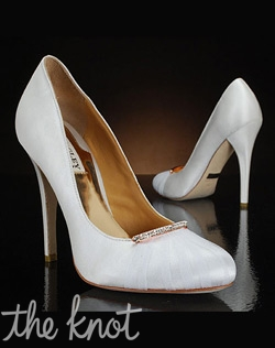White pump with unique decoration at the toe, tulle overlay, and a rhinestone barrette.