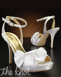 Peep-toe shoe decorated with giant bow detail on the outside of the foot and ankle strap.