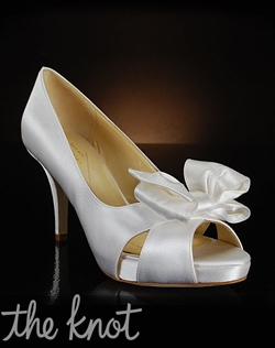 Peep-toe pump features covered platform and bow detail.