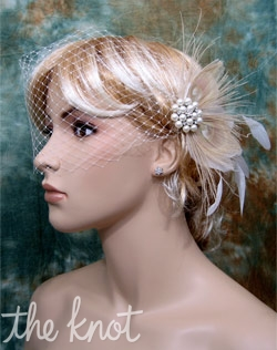 Ivory French net birdcage veil features feather, comb, pearl button, and rhinestones.