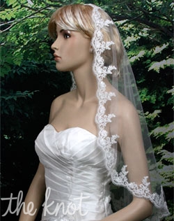 Mantilla-style elbow-length veil features Alencon lace trim. Also available in fingertip length.